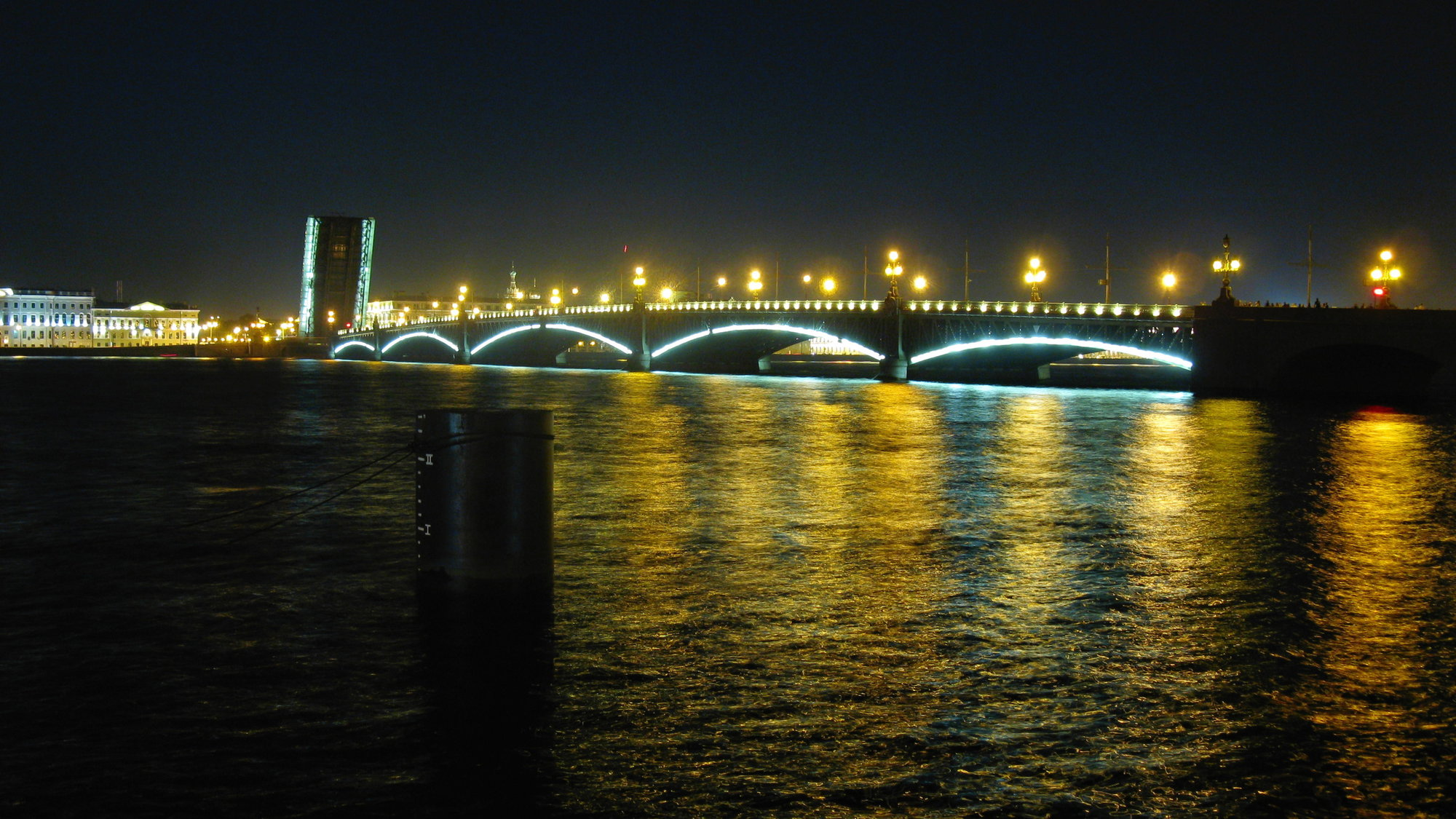 illuminated riverbank and the bridges across the Neva