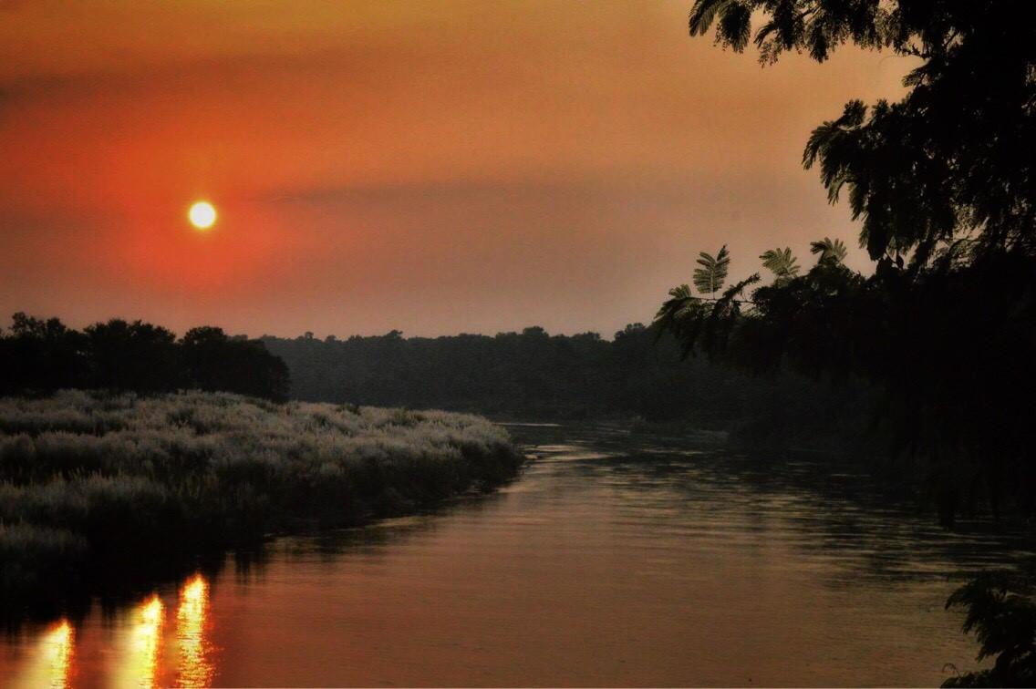 захватывающий закат солнца с берега реки Рапти
