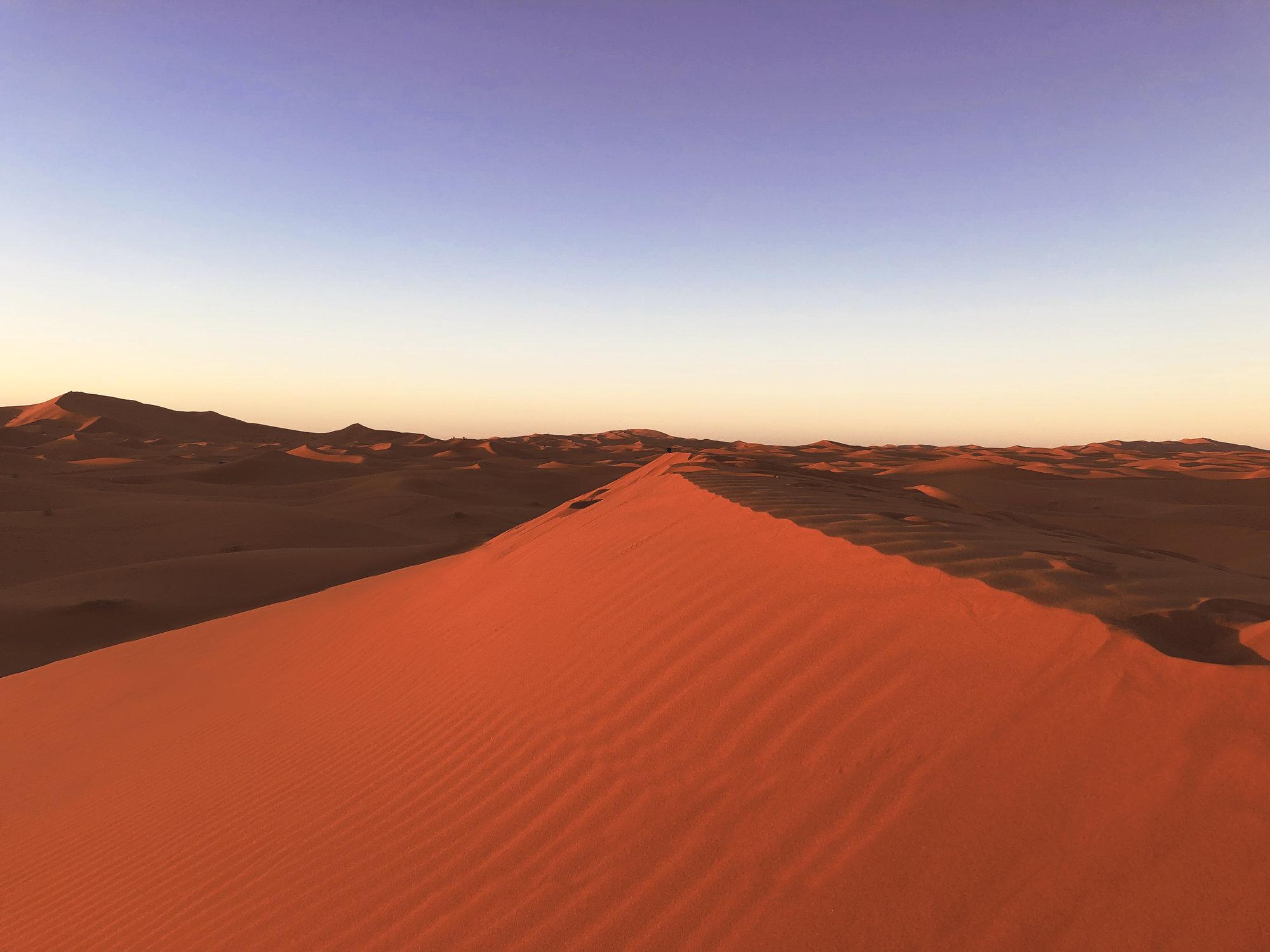 duny zaliate zapadajúcim slnkom