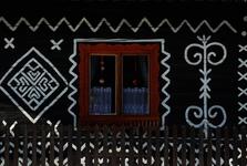 bílé ornamenty na fasádě čičmanských dřevěnic podobné výšivce