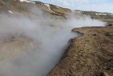 silný vítr si pohrává s kouřem vycházejícím z horké bahenní tůně