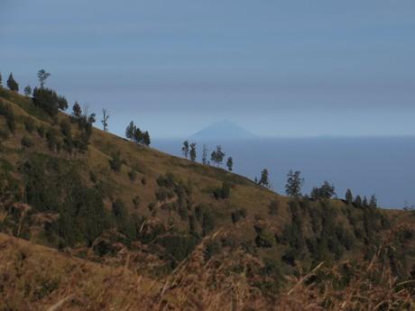 v pozadí břehu kráteru je patrná sopka Agung na Bali