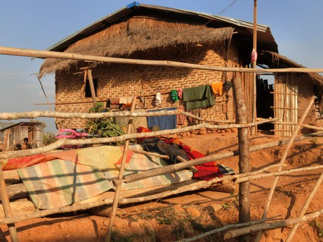 hanging laundry in front of a typical Burmese dwelling