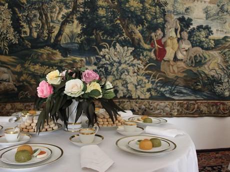 деталь выставки о застолье дворянства с гобеленами на заднем плане